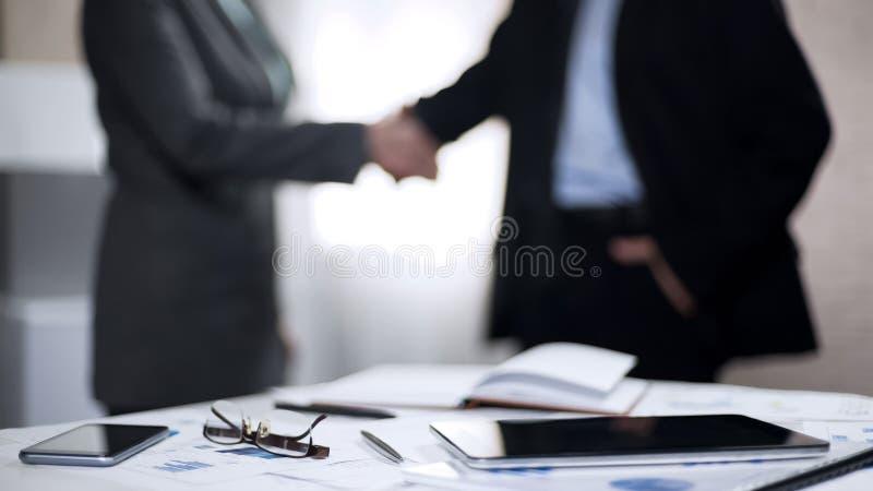 男人和妇女握手在办公室,商务伙伴签合同,联合标志 库存照片