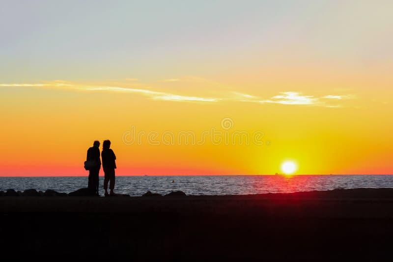 男人和妇女敬佩在海滩的五颜六色的日落 免版税库存照片