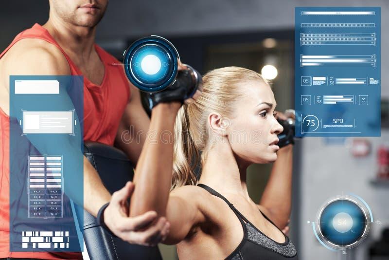 男人和妇女有哑铃的在健身房 库存照片