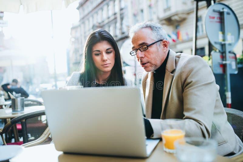 男人和妇女有坐在一个咖啡馆的膝上型计算机的商务伙伴在城市,谈话 图库摄影