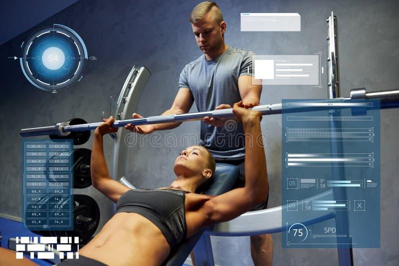男人和妇女有屈曲肌肉在健身房的杠铃的 免版税库存图片