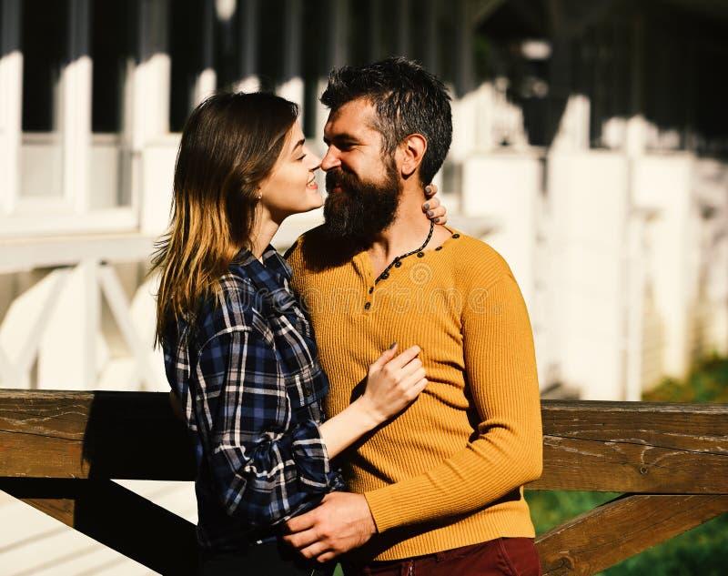 男人和妇女有愉快的面孔的在白色大厦背景 女孩和有胡子的人或愉快的恋人在日期拥抱 库存图片