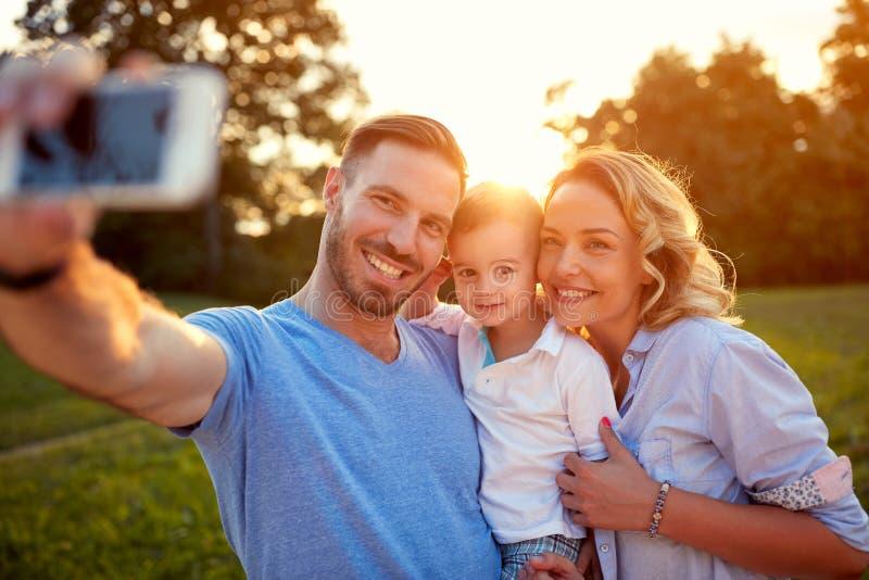 男人和妇女有拍照片的年轻儿子的 库存图片