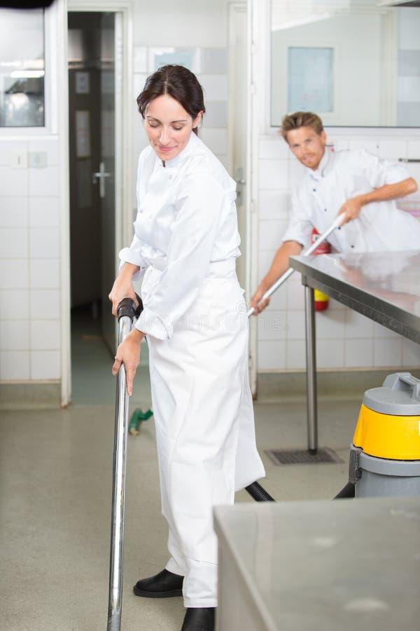男人和妇女清洁地板在profesional厨房里 免版税库存图片