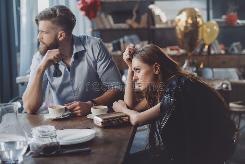 男人和妇女用咖啡在杂乱屋子里 免版税库存照片