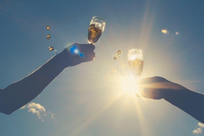 男人和妇女的手使葡萄酒杯闪耀的白葡萄酒叮当响 库存照片