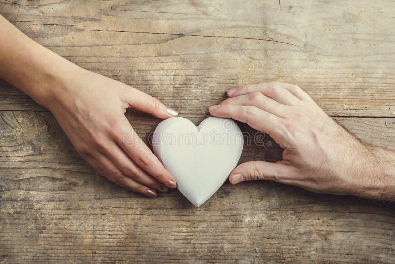 男人和妇女的手通过心脏连接了 免版税库存照片