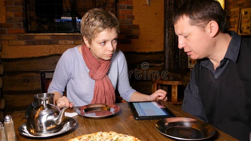 男人和妇女聊天在咖啡馆的商务伙伴 免版税库存图片