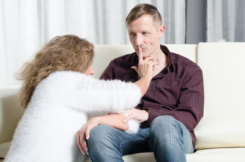 男人和妇女谈话在长沙发-他亲吻她的手指 图库摄影