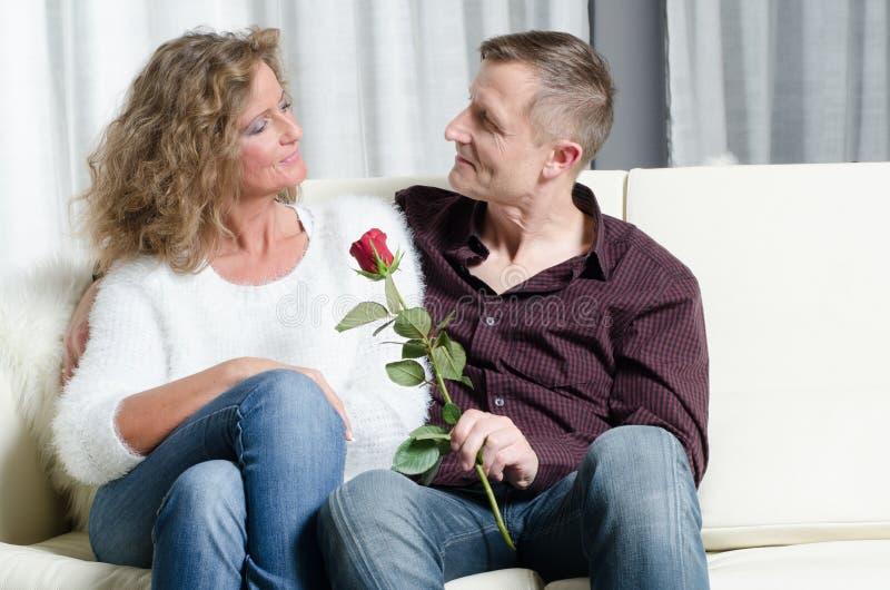 男人和妇女谈话在长沙发-他给她一朵玫瑰 免版税库存图片