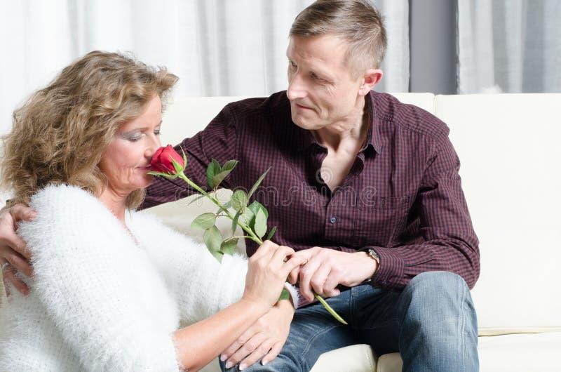 男人和妇女谈话在长沙发-她嗅到玫瑰 库存图片