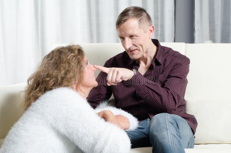 男人和妇女谈话在长沙发-他有他的在她的鼻子的手指 库存照片