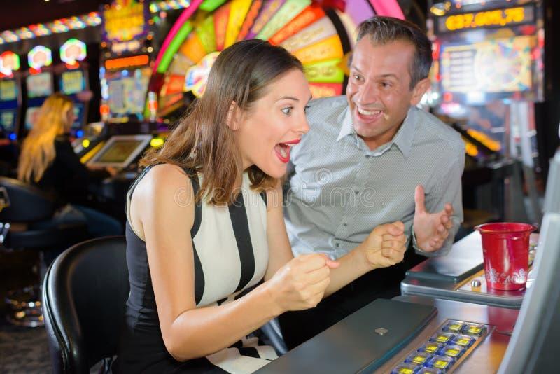 男人和妇女赢取的赌博娱乐场老虎机 免版税图库摄影