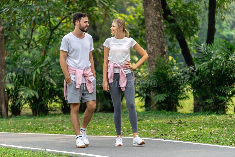 男人和妇女走在公园的夫妇恋人 免版税库存照片