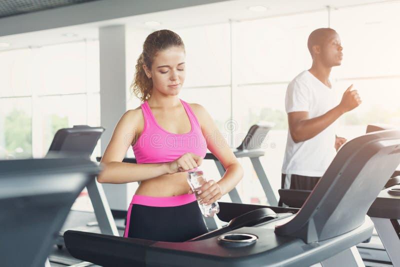 男人和妇女,在健身房的夫妇在踏车 库存图片