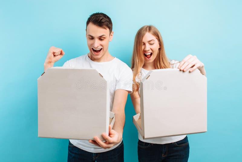 男人和妇女,在蓝色背景拿着箱子用意大利比萨,放松 免版税库存照片