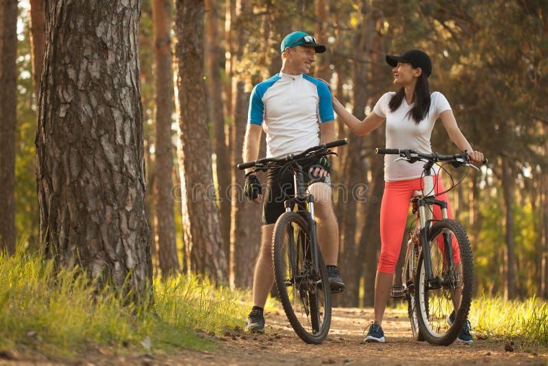 男人和妇女 去循环在森林 对自然的自行车 免版税图库摄影