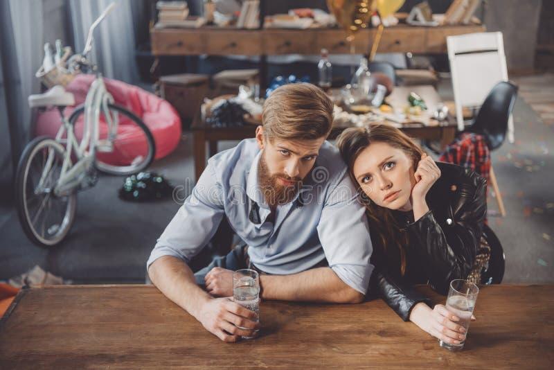 男人和妇女以宿酒与医学在杂乱屋子里 免版税库存图片