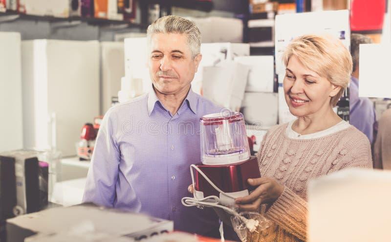 男人和妇女47-57岁在家庭买ap商店  库存图片