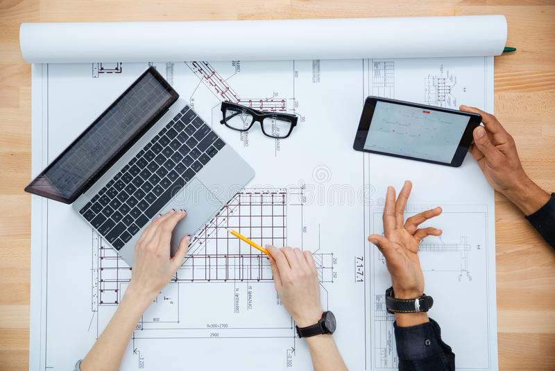 男人和妇女建筑师顶视图disuccing图纸的 免版税图库摄影