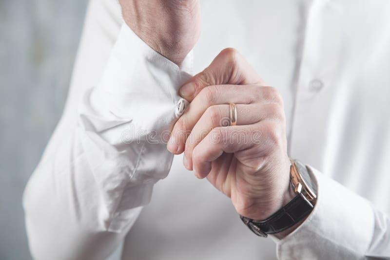男人把扣子扣在衬衫上 库存照片