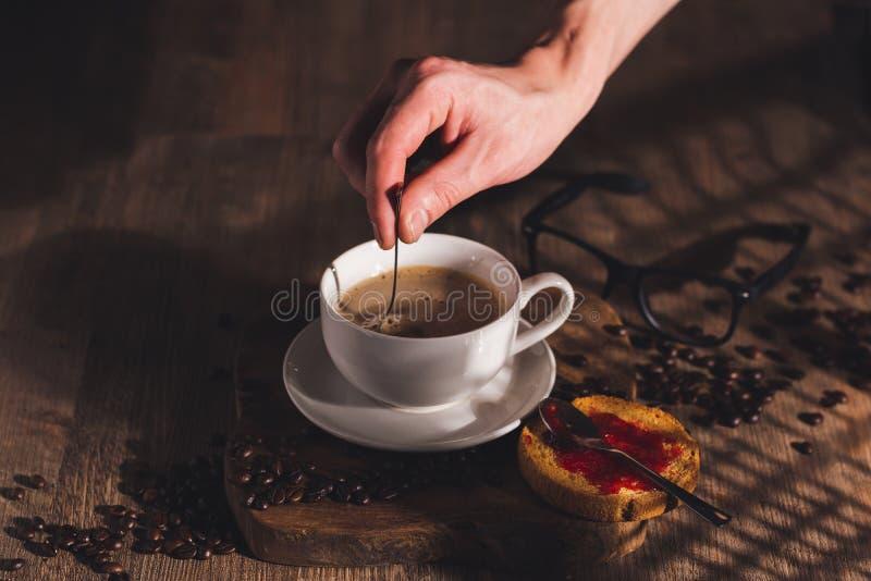 男人把糖倒入一杯咖啡 免版税图库摄影