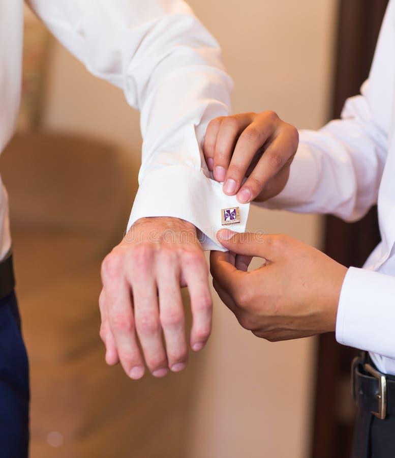 男傧相投入链扣特写镜头的帮助新郎 免版税库存图片