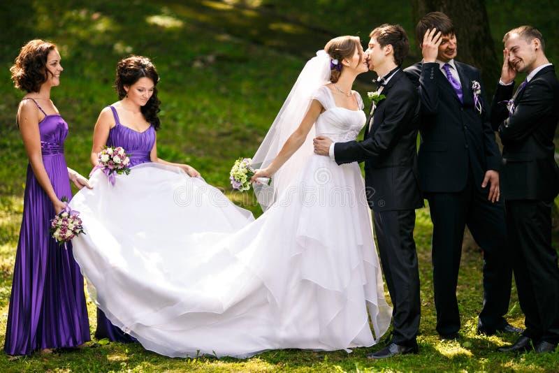 男傧相看起来在一对亲吻的婚礼夫妇后的滑稽的身分 免版税库存照片