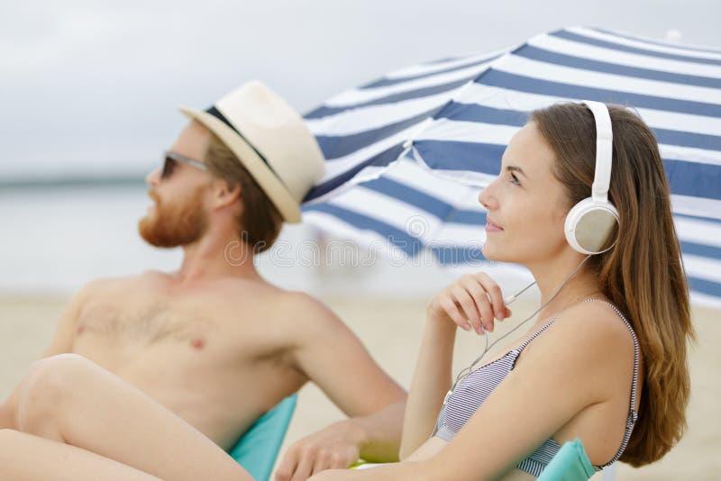 男女在沙滩上听音乐 库存照片