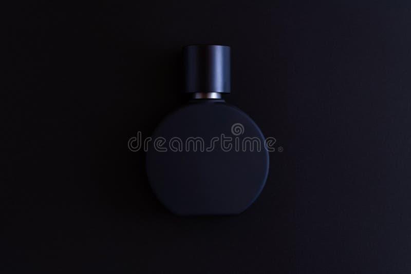 男女皆宜的香水特写镜头的黑表面无光泽的瓶在黑暗的背景,假装,从上面射击了 免版税库存照片