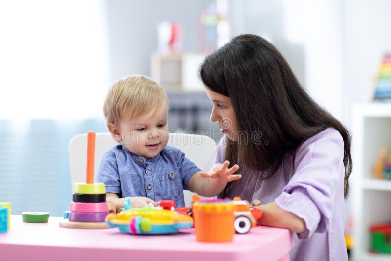 男婴使用与母亲或老师在托儿所或日托中心 免版税库存照片