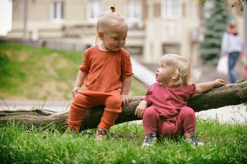 男婴和使用的女婴,当坐绿草时 图库摄影