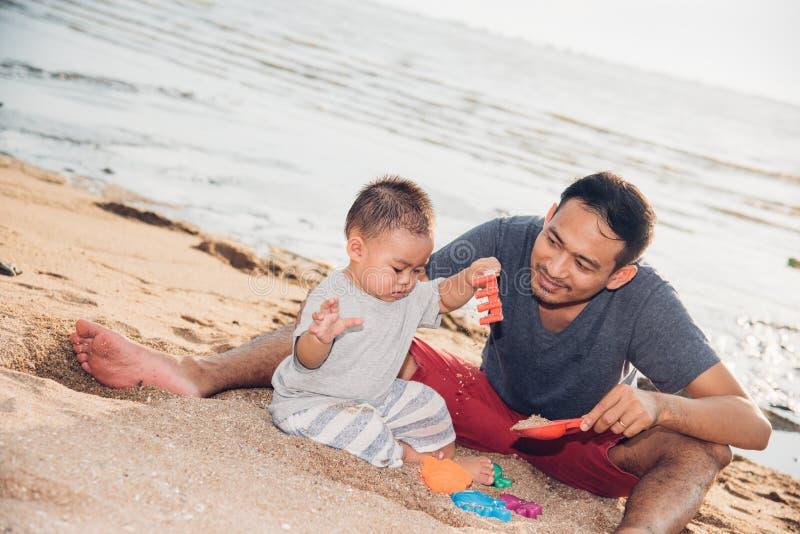 男婴和演奏在沙子海滩的父亲爸爸乐趣 库存图片