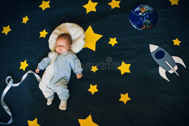 男婴在满天星斗的天空的背景睡觉与火箭和行星的 免版税库存图片