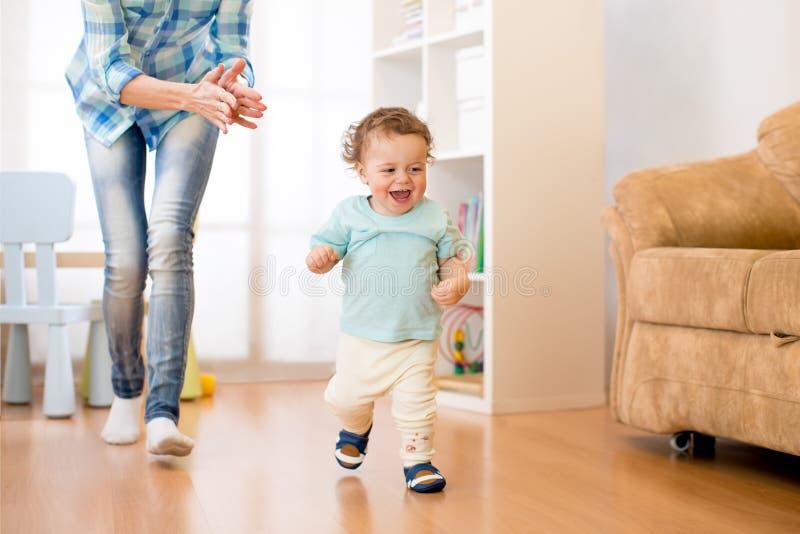 男婴获得跑一个的乐趣在有他的母亲的客厅 图库摄影