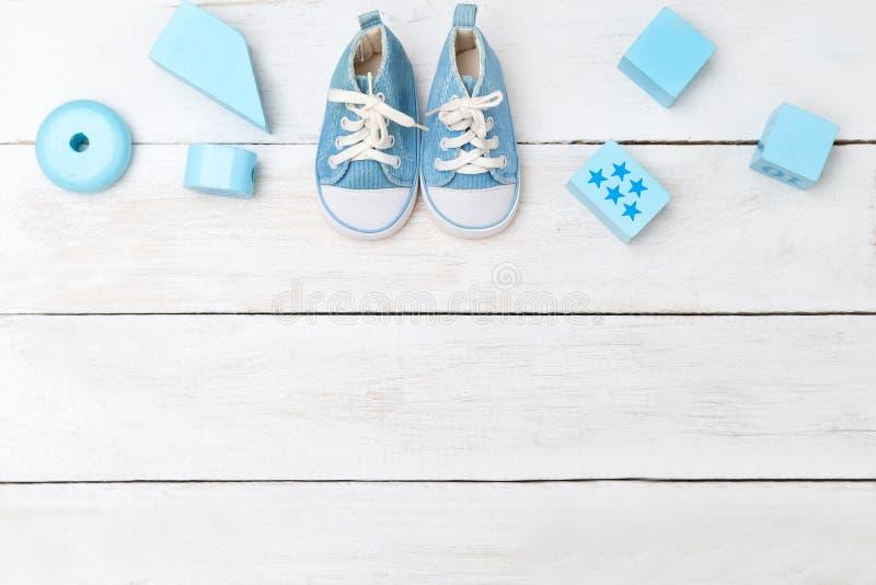 男婴蓝色鞋子和木玩具在白色木背景 库存图片