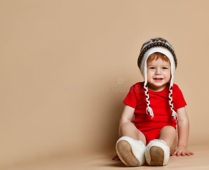 男婴衣物,帽子的,孩子坐愉快的孩子 图库摄影