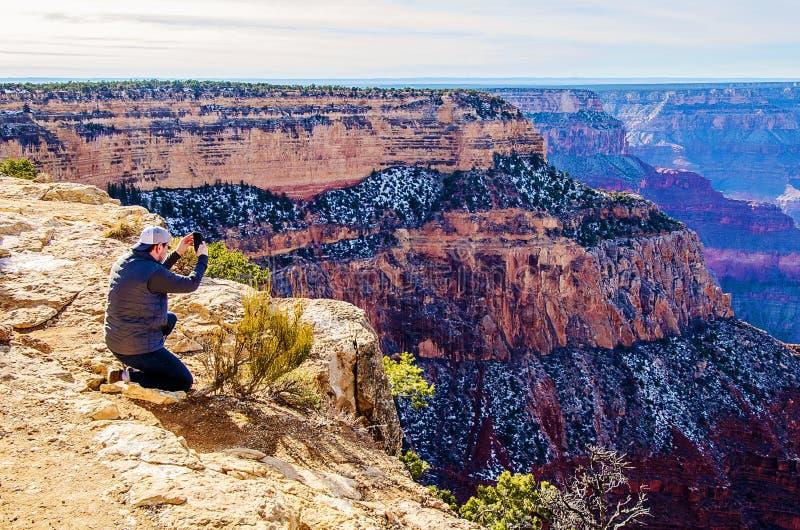 男子在南亚利桑那大峡谷边缘拍照 免版税库存照片