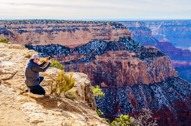 男子在南亚利桑那大峡谷边缘拍照 免版税库存图片