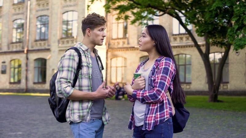 男学生谈话与美丽的女性朋友,谈论测试在学院附近 免版税图库摄影