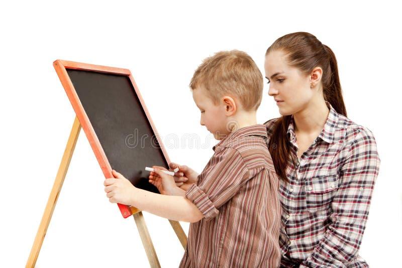 男孩、妇女和黑板。文字 库存照片