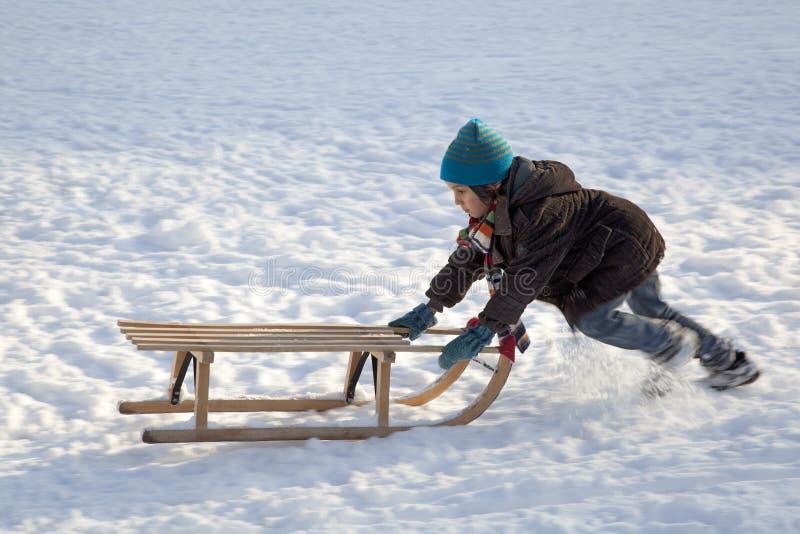 男孩一点推进的雪撬uphills 库存照片