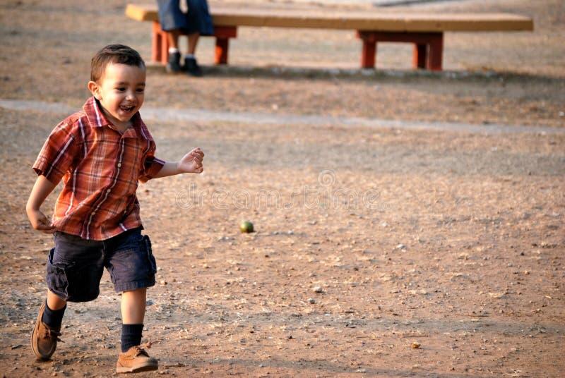 男孩一点运行的微笑 图库摄影