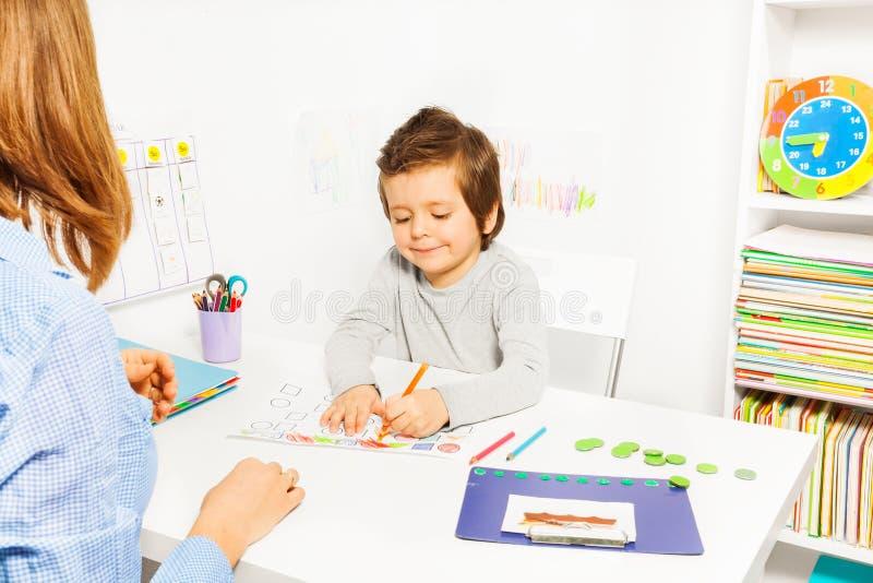 男孩上色形状在与近治疗师的ABA期间 图库摄影