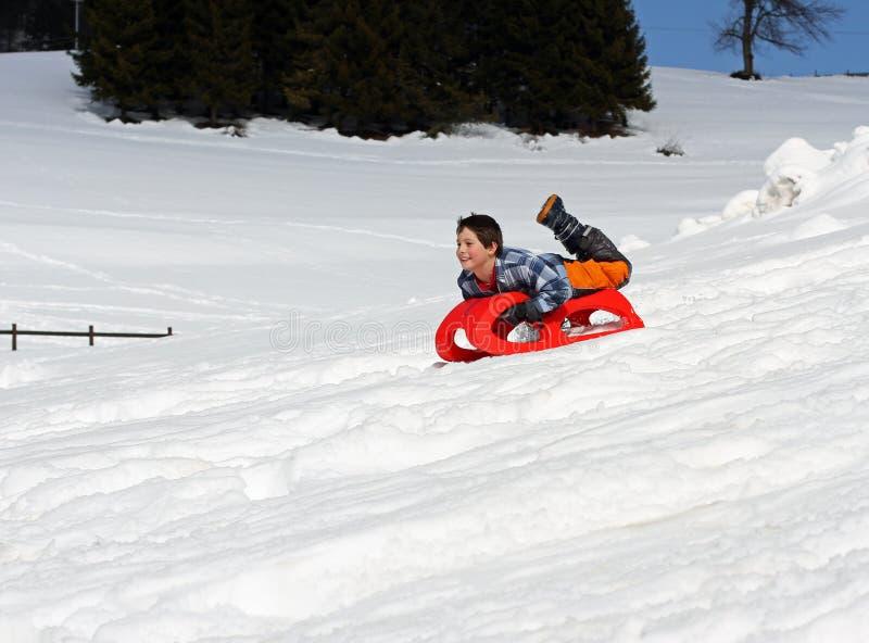 男孩下来与红色雪撬 免版税库存图片