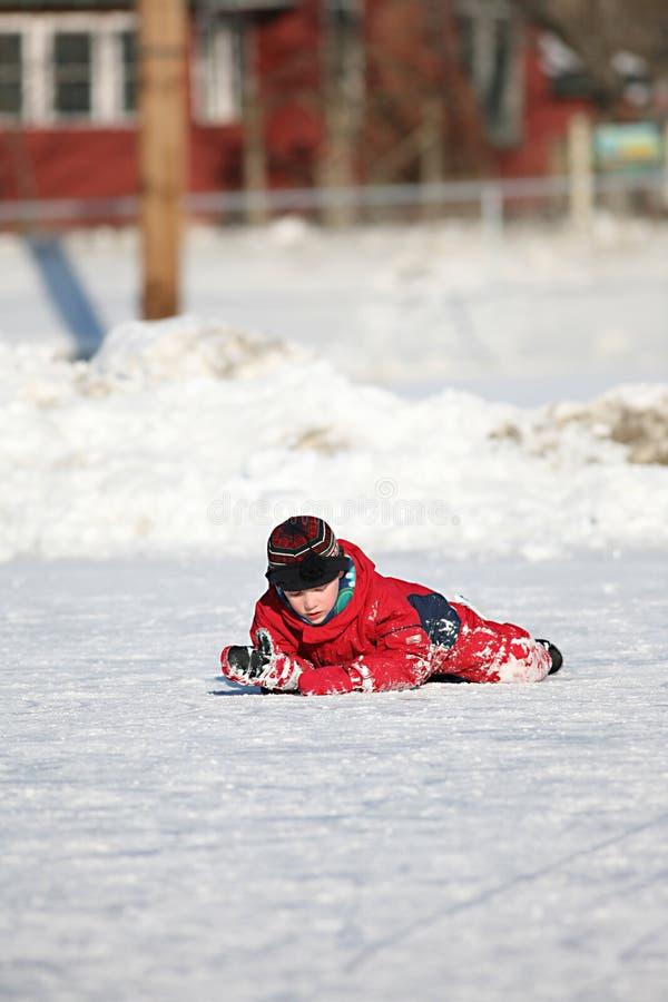 男孩下来跌倒了溜冰场滑冰 免版税库存照片