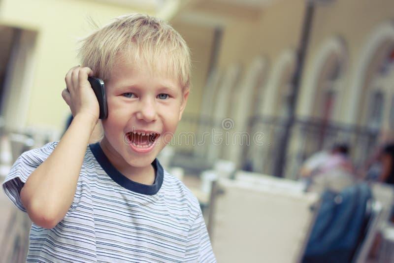 男孩与一个手机讲话 库存图片