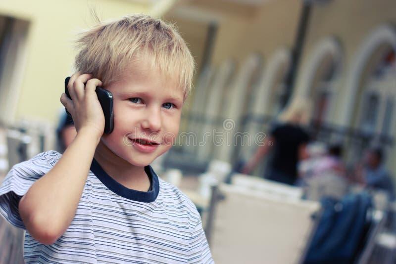 男孩与手机讲话在超级市场 免版税库存图片