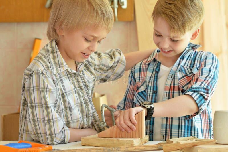 男孩与木头一起使用在车间 图库摄影