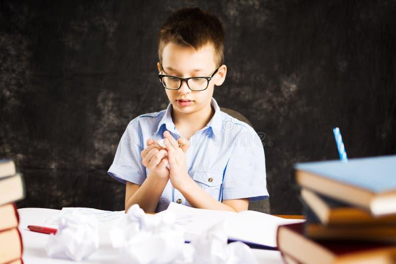 男孩丢掉与家庭作业问题的纸 库存图片